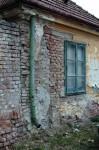 Abgebröckelter Putz, gelbe Fassade, Lehmziegel, ein grünes Regenrohr und ein altes Kastenfenster - das hat Flair !